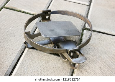 One rusty iron trap lying on the stone floor, cocked