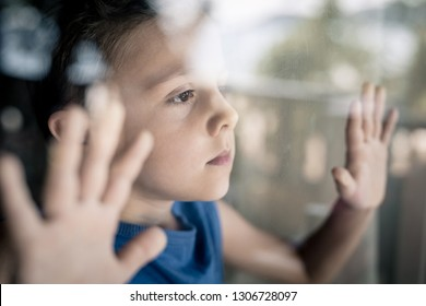 one sad little boy standing near the window at the day time. Concept of sorrow.