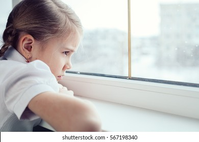 one sad little girl sitting near the window at the day time. Concept of sorrow.