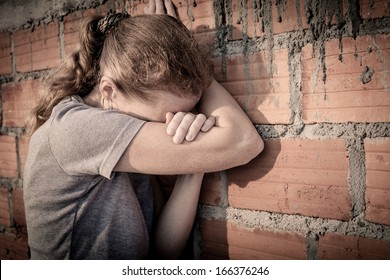 one sad woman sitting  near a brick wall