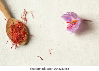 one saffron flower and a lot of drying stigma in a wooden spoon