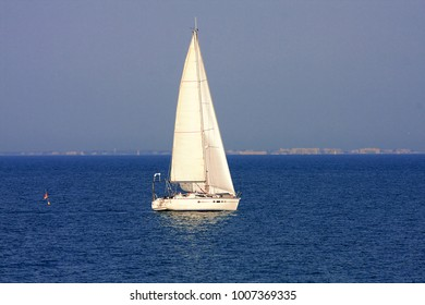 one  sail boat sailing on calm blue water