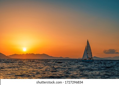 One sailing boat floating on the blue Aegean Sea during sunrise / sunset with open main sail and genoa. Orange sky and sun with islands in background for copy space