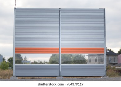 One section of a acoustical barrier or a sound wall. Reducing of noise and sound pollution made by transportation. New road construction site.