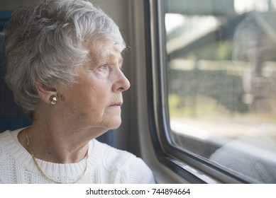 One senior woman looking out of the window on a train