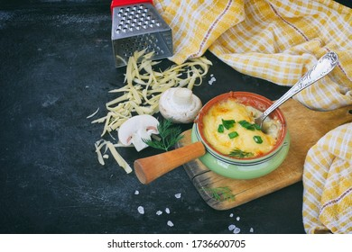 una juliana al horno con paladines, cebollas y queso sobre mesa negra, sobre tablero de madera, toalla a cuadros, rallador de queso
