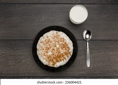 One serving of rice pudding on a black plate with ground cinnamon and sticks on a dark wooden table also with a glass of milk.