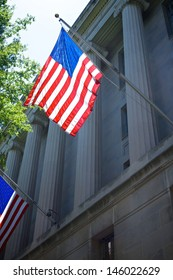 One of several US flags hangs from the side of the Department of Justice in Washington DC