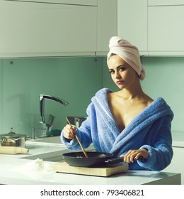 One sexual beautiful sensual female housewife in blue terry dressing gown and towel turban on head with bare shoulders standing in kitchen cooking breakfast from fried eggs in morning life, square