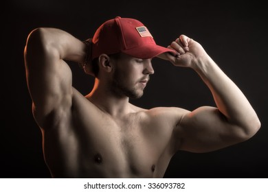 One sexual strong young man with muscular body in red sport  cap standing posing in studio on black background, horizontal picture