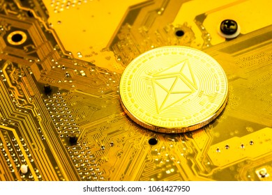 One shiny golden Ethereum (ETH) physical coin on a computer circuitboard or motherboard Ethereum is a digital blockchain cryptocurrency