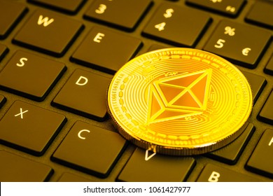 One shiny golden Ethereum (ETH) physical coin on a computer keyboard. Ethereum is a digital blockchain cryptocurrency