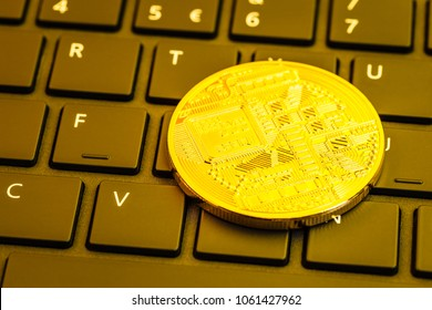 One shiny golden generic cryptocurrency physical coin on a computer keyboard. A digital blockchain cryptocurrency is an anonymous form of payment