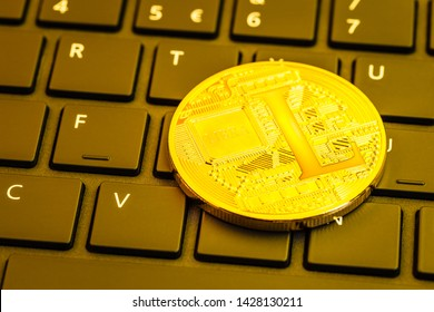 One shiny golden libra cryptocurrency physical coin (facebook cryptocurrency) on a computer keyboard. A digital blockchain cryptocurrency is an anonymous form of payment