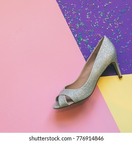 one shiny silver shoe with high heel on pink, yellow and ultra violet background with confetti. the magical concept of the holiday. fashion minimal