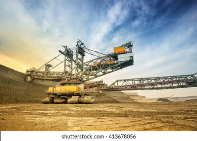 One side of huge coal mining drill machine photographed from a ground with wide angle lens. Mining site and dramatic and colorful sky in background. Low angle shot.