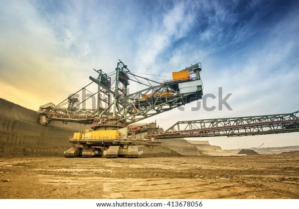 Eine Seite der riesigen Kohlebergbaubohrmaschine fotografiert von einem Boden mit Weitwinkelobjektiv. Mining-Ort und dramatische und bunte Himmel im Hintergrund. Niederwinkelaufnahme.