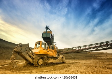 One side of huge mining drill machine connected to transportation facility. Photographed from a ground with wide angle lens. Dramatic and colorful sky in background.