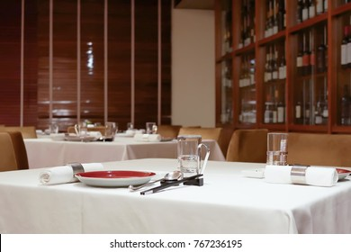 One side of red wine cabinet with glasses and chopsticks at table inside restaurant