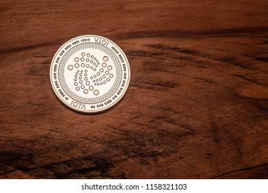 One silver IOTA coin on a dark wood grain background.