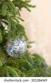 One silver mercury glass ornament on spruce Christmas tree with lights in the background. Shot with copy space.