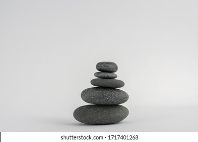 One simplicity stones cairn isolated on white background, group of five white pebbles in tower, harmony and balance