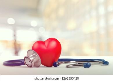 一人の赤い心臓愛の形をした手の練習用ボールと包帯MD医師の聴診器の白い木の背景:病院生命保険のコンセプト:世界の心臓の健康デーのアイデア
