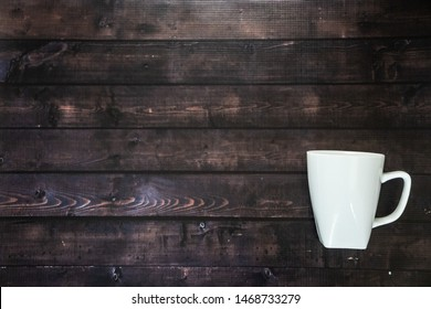 One single coffee mug on wooden table background - 1 java espresso for morning pick me up coffee break with blank empty room for text or copy space. Rustic coffee house look with tasty caffeine.