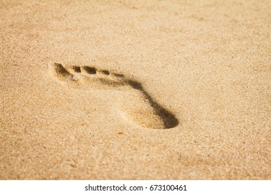 One single footprint of a adult woman in the yellow sand beach.