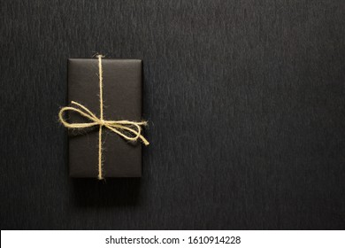 One single gift wrapped in black paper with a bow of packthread on black paper. Photo with copy blank space.