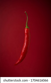 One single hot red chili/chilli peppers on red background