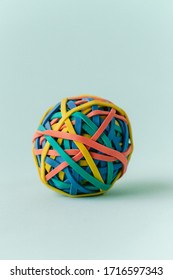 One single multicolored rubber band ball on a green background