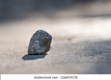 one single stone isolated on a street with blur  colored background, stone is grey and the background is blur, grey and orange, horizontal