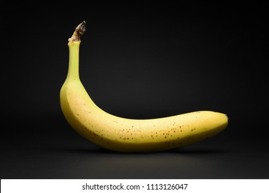 One single yellow banana isolated on black background