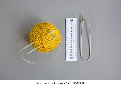 One skein of yellow wool yarn, knitting spokes, measuring ruler and large pin on gray background, handmade, knitting. Close-up. Copy space. Selective focus.