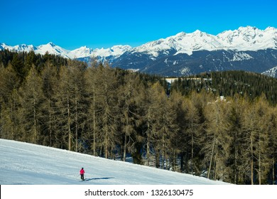 One skier on the snow mountain slopes. landscape with beautiful coniferous forest and blue sky. Kronplatz, Dolomites, South Tyrol, Italy.