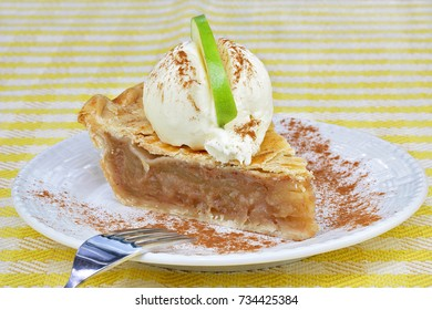 One slice of apple pie with vanilla ice cream on top and a slice of a Granny Smith apple for garnish.
