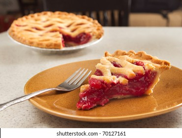 one slice of cherry pie ready to eat with a fork taken from the whole