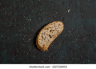 One slice freshly baked homemade whole wheat bread with flaxseeds. Useful dietary bread without yeast. Greenish-brown textured background with slice and bread crumbs
