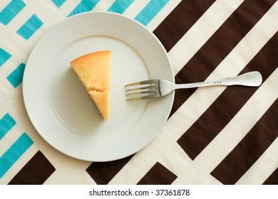 One slice of lemon cake on a white plate