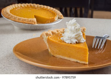 one slice of pumpkin  pie removed from the whole and ready to eat