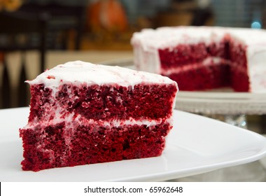one slice of red velvet cake in front of the whole dessert