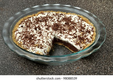 one slice removed from a chocolate cream pie in a glass plate