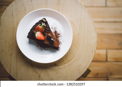 One slice of vegan raw chocolate  cake on wooden table from above. Sugar free, wheat free, dairy free, flourless dessert. Food photo, blog. Healthy eating, copyspace.