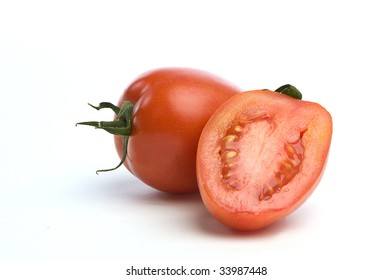 One sliced saladet tomato in front of a whole one over a white background