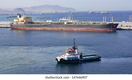 One small boat docked to oil tanker in port of Fujairah (United Arab Emirates)