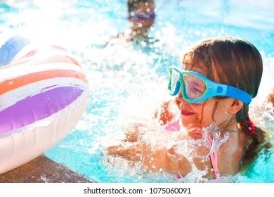 One small girl having fun in outdoor pool. Summer vacation concept