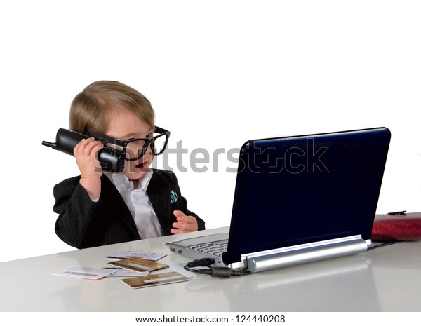 One small little girl (boy) calling phone, wearing black suit and glasses. Computer, credit cards are on table. Business concept. Isolated object.