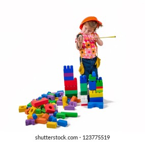 One small little girl wearing orange hard hat, work boots, blue jeans, yellow gloves measuring toy blocks with the measuring tape.