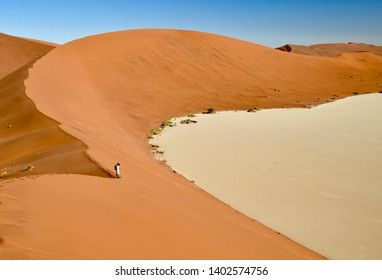 One small man standing in great sand red dunes around white salt pan in Sossusvlei Namibia
